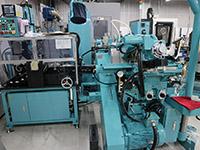 シャンクの高精度化追求に日進機械のセンタレス研削盤が導入された。1時間300本の検査ができる測定機能もつけられている