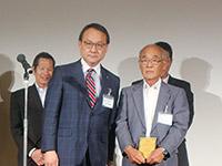 年間表彰の場で特約店代表と記念撮影に収まる金子営業本部長(左)
